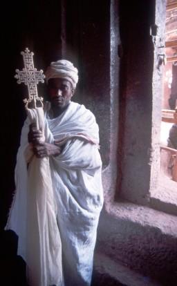 Ethiopie prêtre copte présentant la croix de l'église Bete Maryam. Lalibela est une ville de la région Amhara, dans le nord de l'Éthiopie. Elle est connue pour ses églises uniques, taillées dans la roche, qui datent des XIIe et XIIIe siècles et constituent des sites de pèlerinage pour les chrétiens coptes. Creusés à même la roche, les monolithes souterrains comprennent l'immense Bete Medhane Alem et l'église en forme de croix Bete Giyorgis. Nombre de ces églises sont reliées par des tunnels et des tranchées, et certaines sont ornées de bas-reliefs et de fresques colorées à l'intérieur. Altitude : 2 630 m